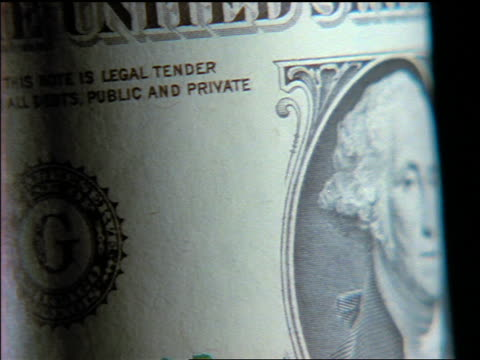 vidéos et rushes de extreme close up zoom out us dollar rolling by camera - billet de banque
