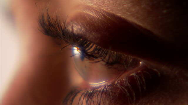 extreme close up_hand-held - a human eye watches and blinks.   - まつげ点の映像素材/bロール