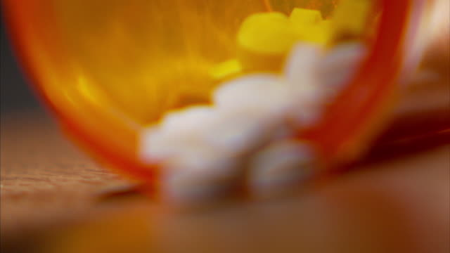 Extreme Close Up_rack-focus static - Pills spill out of a prescription bottle.
