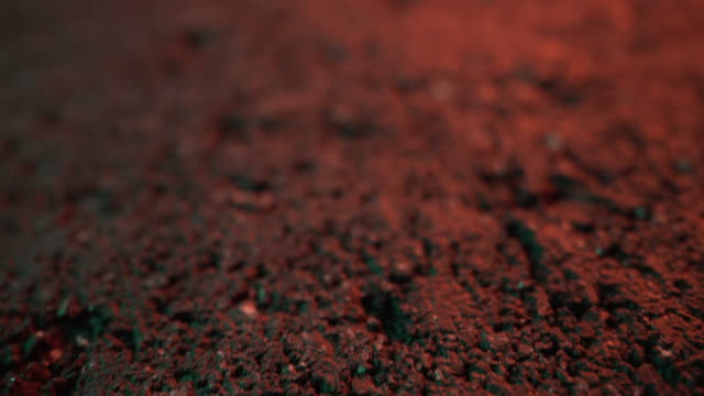extreme close-up artistic unique defocused on foreground macro forward-moving slider flyover shot of pavement, asphalt, or black painted concrete textured pattern background under bright neon orange lighting - pavement stock videos & royalty-free footage