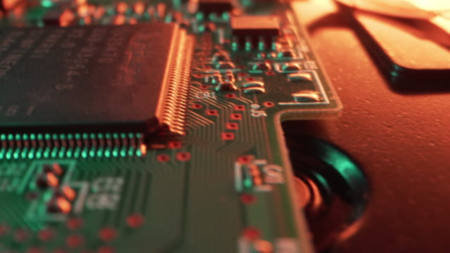 extreme close-up artistic unique macro moving slider flyover shot of computer chips and circuits on a hard disk drive from a computer or server or security or bitcoin mining system under bright neon colored lighting - complexity stock videos & royalty-free footage