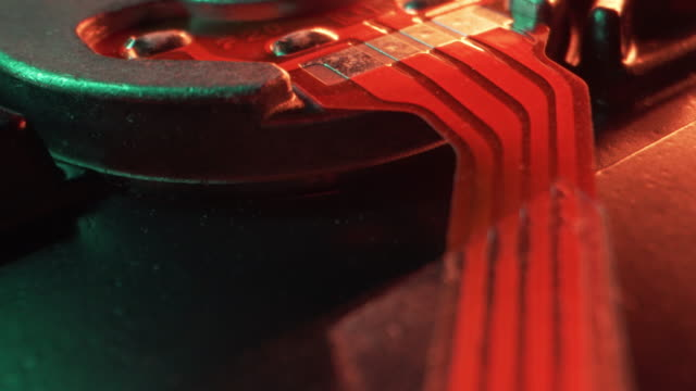 extreme close-up artistic unique macro moving slider flyover shot of ribbon cable for a motor controlled by computer chips and circuits on a hard disk drive from a computer or server or security or bitcoin mining system under bright neon colored lighting - server room stock videos & royalty-free footage