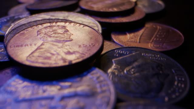 stockvideo's en b-roll-footage met extreme close-up macro bewegende schuifschot van amerikaanse muntmuntstukken die omhoog op een houten lijst worden opgestapeld - samenzwering