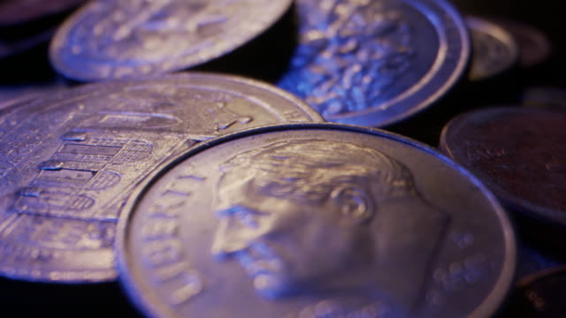 extreme close-up macro moving slider shot of american currency coins piled up on a wooden table - coin stock videos & royalty-free footage