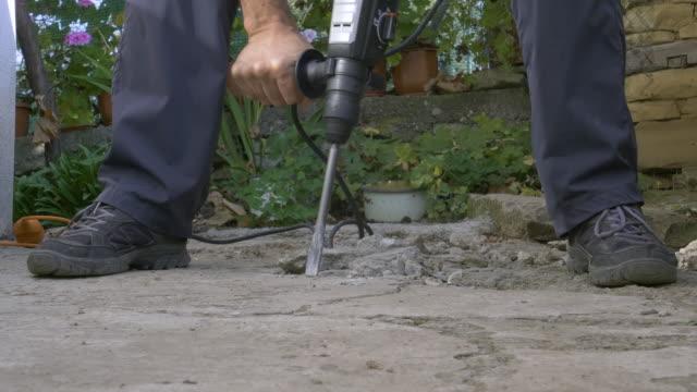 extreme nahaufnahme eines bauarbeiters mit jackhammer. arbeiten auf einer baustelle. bohren, baustelle, bauindustrie, bremsen eines felsens - hammer stock-videos und b-roll-filmmaterial