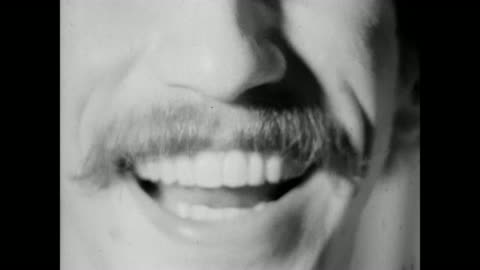 extreme closeup of a man with a mustache and white teeth, talking directly to camera; film is over-cranked, features jump-cuts and mylar splices, retro 16mm black and white experimental film with scratches, gate weave and grainy image. - moustache stock videos & royalty-free footage