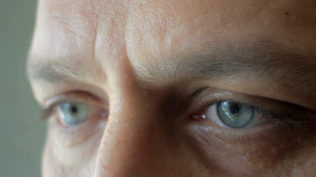 vídeos de stock, filmes e b-roll de close-up extremo dos olhos de um homem olhando para longe - primeiríssimo plano