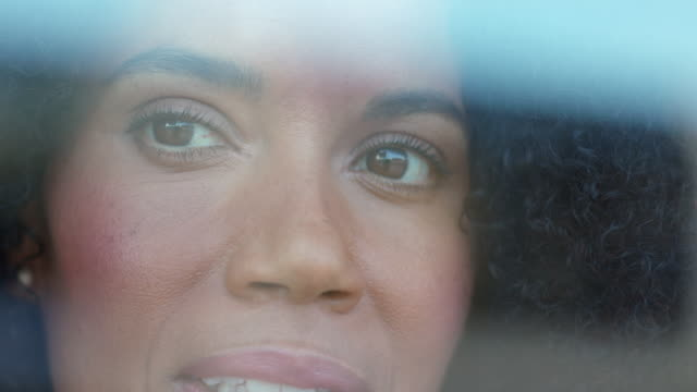 Extreme close-up of a mixed race, middle-aged woman with natural hair laughing as she turns to and from camera through window.