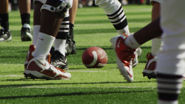 Extreme closeup of football on the line of scrimmage; legs and shoes of various players walk through frame.