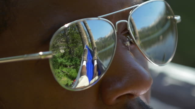 Extreme close-up of man wearing sunglasses resting in a hammock near a mountain lake. - Slow Motion