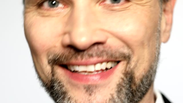 Extreme close-up of mature man smiling on white