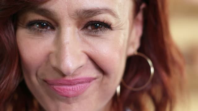 stockvideo's en b-roll-footage met extreme close-up of middle-aged woman with red hair smiling at camera, in front of a blurred background. - oudere vrouwen