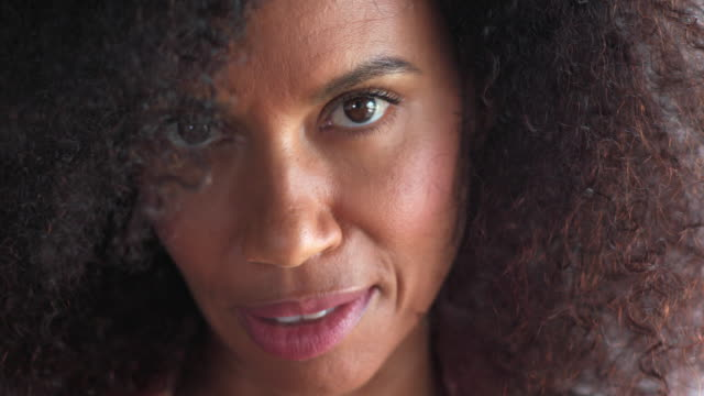 extreme close-up of mixed race, middle-aged woman with natural hair looks up and smiles at camera. - frauen über 40 stock-videos und b-roll-filmmaterial