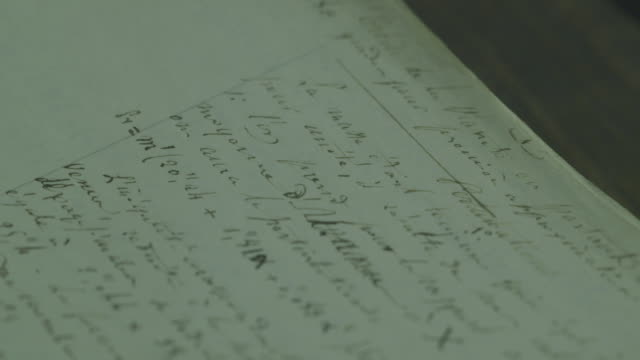 Extreme close-up of pages of complicated mathematical formulae from the 19th Century being turned over.
