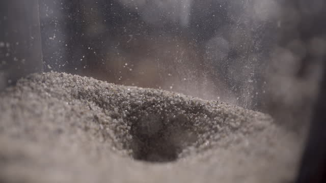 extreme closeup of sand falling in the top part of an hourglass - gフォース点の映像素材/bロール