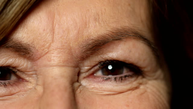 extreme close-up of senior woman blinking her eyes - primissimo piano video stock e b–roll