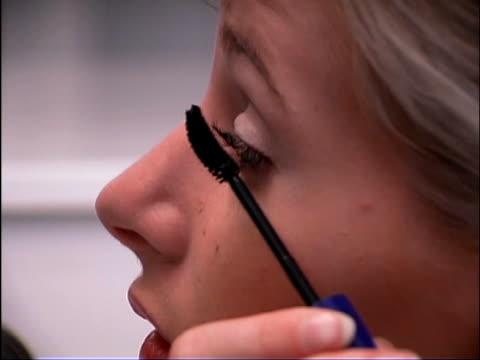 extreme close-up of teen girl's face as she applies mascara to her left eye. - endast en tonårsflicka bildbanksvideor och videomaterial från bakom kulisserna