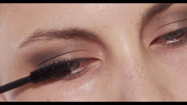 vidéos et rushes de extreme close-up of woman applying mascara to top lashes - appliquer