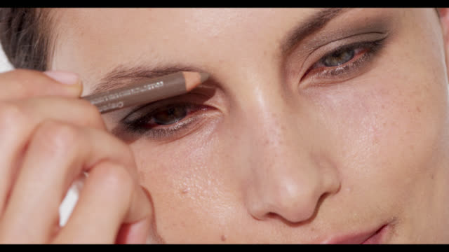 Extreme close-up of woman defining camera left eyebrow with brown eyebrow pencil