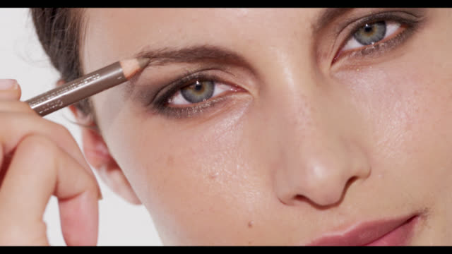 extreme close-up of woman defining camera left eyebrow with brown eyebrow pencil - urbanlip stock videos & royalty-free footage