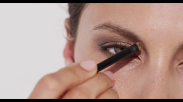Extreme close-up of woman defining camera left eyebrow with brush