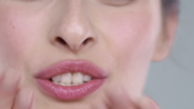 extreme close-up of woman focussing on eyes and blowing kiss to camera - lipgloss stock-videos und b-roll-filmmaterial