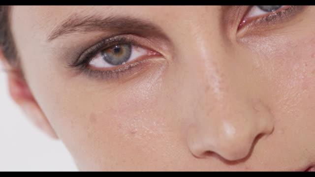 vídeos y material grabado en eventos de stock de extreme close-up of woman's eyes looking into camera and blinking once - una mujer de mediana edad solamente