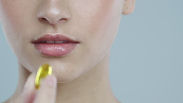 extreme close-up of young woman with glowing skin taking a vitamin pill - vitamin a nutrient stock videos and b-roll footage