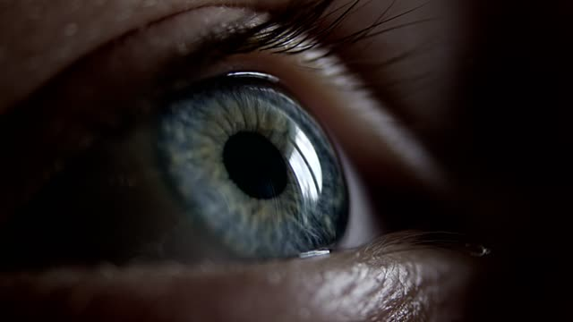 extreme closeup on blue human eye - luminosità video stock e b–roll