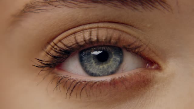 extreme closeup on bright blue eye. beautiful female face - eye stock videos & royalty-free footage