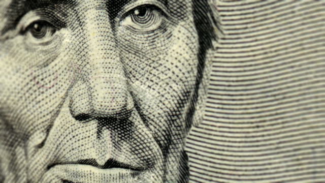 extreme close-up pan across an american five dollar bill. - five dollar bill stock videos & royalty-free footage