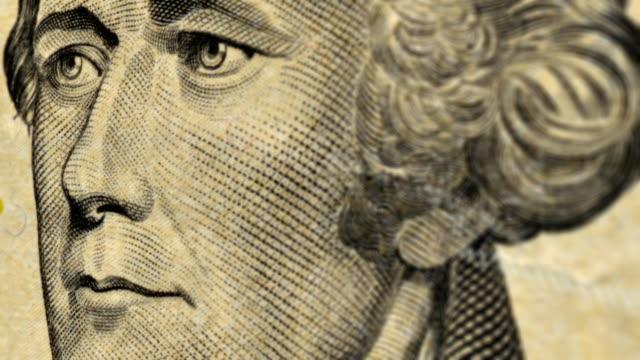 extreme close-up pan across an american ten dollar bill. - banconota da 10 dollari statunitensi video stock e b–roll