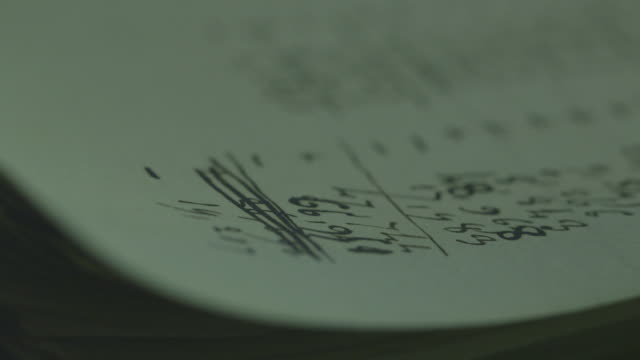 Extreme close-up pan onto handwritten 19th Century mathematical calculations.