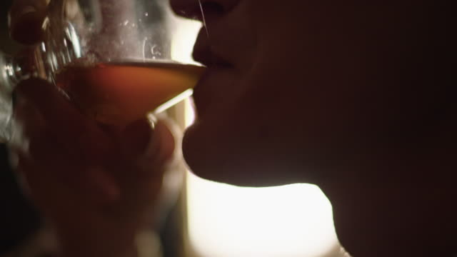 reenactment extreme close-up shot of a man drinking whiskey from a snifter in a bar during the 1940s - produced segment stock videos & royalty-free footage
