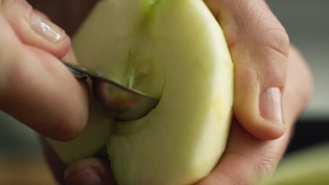 extreme close-up shot of a woman's hands coring a peeled and halved apple with a small spoon - pastry dough stock videos & royalty-free footage