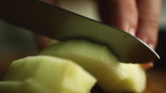 extreme close-up shot of a woman's hands cutting a peeled and halved apple on a wooden kitchen knife with a kitchen knife - apple fruit stock videos & royalty-free footage