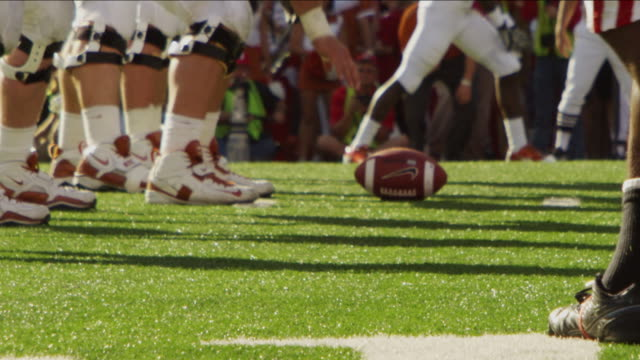 extreme closeup slow motion of football on the line of scrimmage; both teams approach the line into position. - nebraska stock-videos und b-roll-filmmaterial