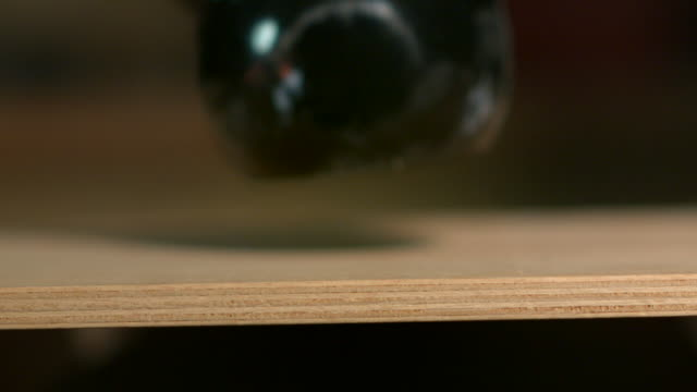 extreme close-up, slow-motion sequence showing a weight being dropped onto a piece of plywood board. - ウェイトトレーニング用器具点の映像素材/bロール