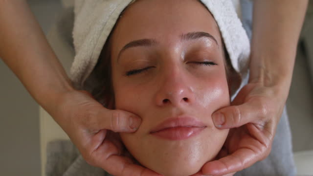 extreme close-up video of a woman enjoying a face massage - reclining stock videos & royalty-free footage