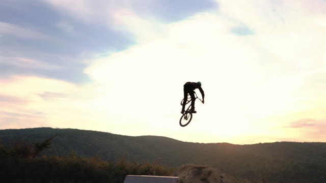 extreme cyclist jumping over sports ramp and backflipping over dirt hills at sunset. - bmx cycling stock videos and b-roll footage