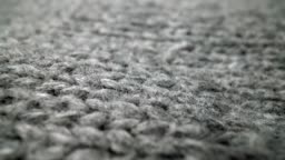 Extreme detail view of sheep wool cloth texture flowing in macro dolly shot.