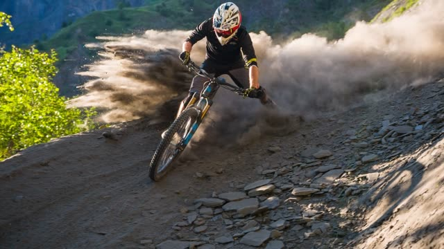 extreme downhill mountain biker on dirt road making a turn, leaving a cloud of dust behind - bicycle trail outdoor sports stock videos & royalty-free footage