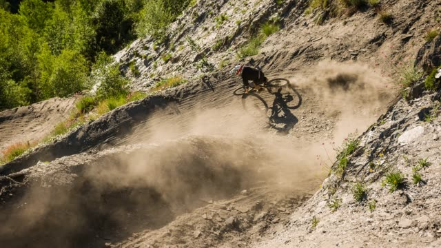 extreme downhill mountain biker on dirt road making a turn, leaving a cloud of dust behind - andare in mountain bike video stock e b–roll