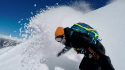 SELFIE: Extreme freeride snowboarder doing powder turns off-piste in mountains