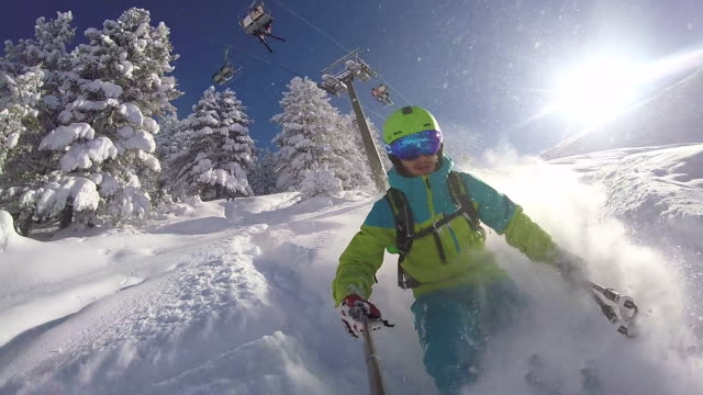 slow motion: extreme freestyle skier riding fresh powder snow in sunny mountains - skiing stock videos & royalty-free footage