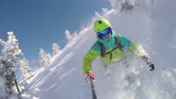 SLOW MOTION: Extreme freestyle skier skiing fresh powder snow in snowy mountains