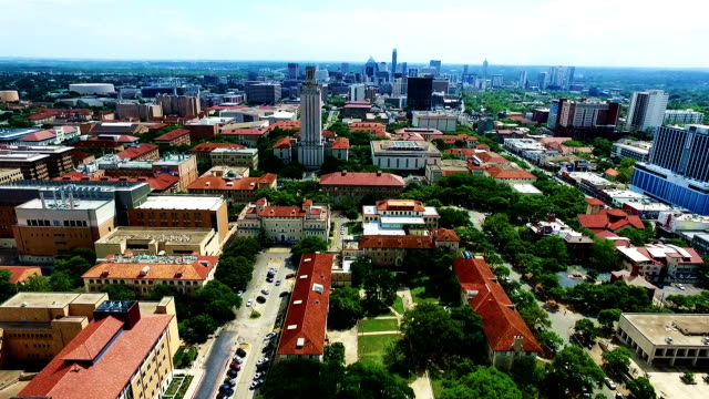 extreme high contrast far away shot with ut tower and skyline in the distance aerial fly by austin texas over university of texas - mass unit of measurement stock videos and b-roll footage