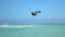 SLOW MOTION CLOSEUP: Extreme kite girl kiteboard jumping rally in blue lagoon