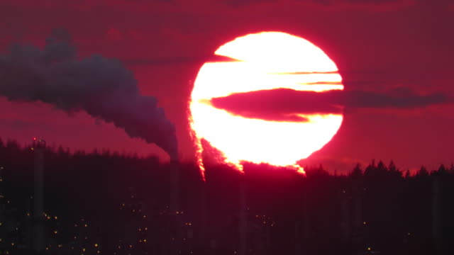 extreme large sunset with polluting smokestack  against red sky - anacortes stock videos & royalty-free footage