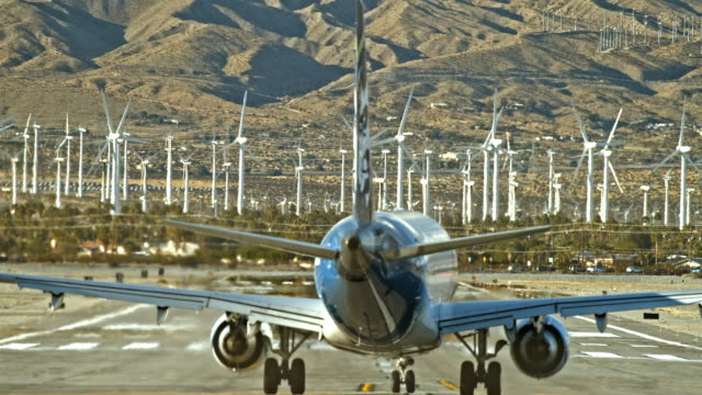 extreme long lens rear view of alaska airlines jet making turn on to airport runway as jet engine exhaust fills the air against backdrop of clean energy wind farm in far distance - turbine stock-videos und b-roll-filmmaterial